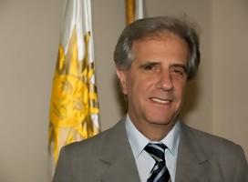 El Dr Vázquez. sonriente. de fondo, la bandera de Uruguay