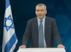 El ministro Elkin hablando, a su lado, una bandera de Israel
