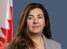Mujer, mirando de frente, con la bandera de Bahrein a su izquierda