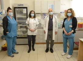 Cuatro miembros de un equipo médico, uniformados con ropa de hospital