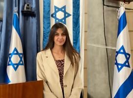 Una joven mirando a la cámara, rodeada de banderas de Israel