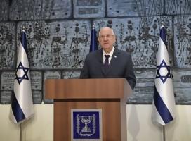 Rivlin de pie, en podio de oradores con el escudo de Israel, de fondo una obra de arte a sus dos costados, la bandera de Israel