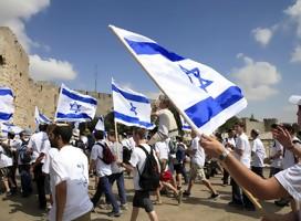 Jóvenes vestidos con remeras blancas, con banderas de Israel